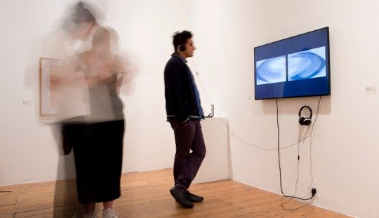 a man watches a video on a screen in a gallery