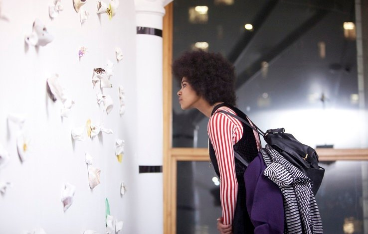 a girl bends over looking intently at the wall covered in paper objects that have different smells in a gallery space