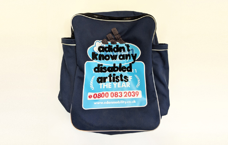 a navy rucksack on a cream background has a baby blue motif on it but embroidered over the top in black thread reads adidnt know any disabled artists with a the three adidas stripes at the top
