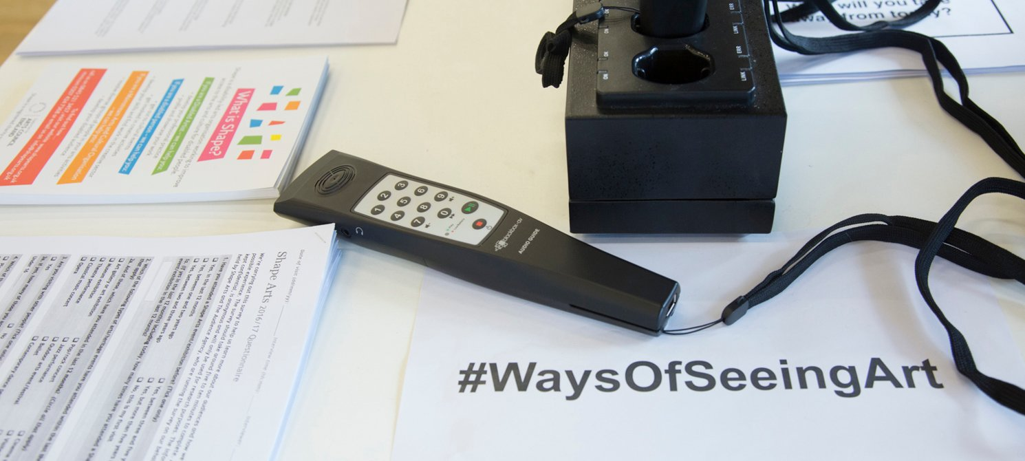 Close-up of an audio description handset sitting on a table of leaflets, one of which has #waysofseeingart printed on it