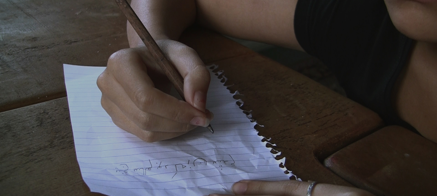 still from a video by Maryam Tafakory: a young woman writing on a plain page