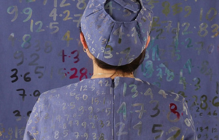 Photo of a person wearing lilac clothes and a hat covered in painted numbers with their back to the viewer, facing a background which is the same lilac covered in painted numbers