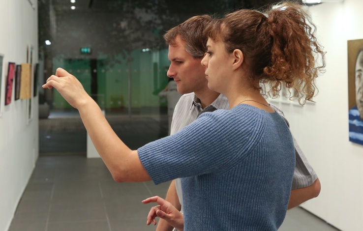 A white women with brown curly hair is looking and pointing at a painting in a gallery and audio describing it to a white man with brown hair
