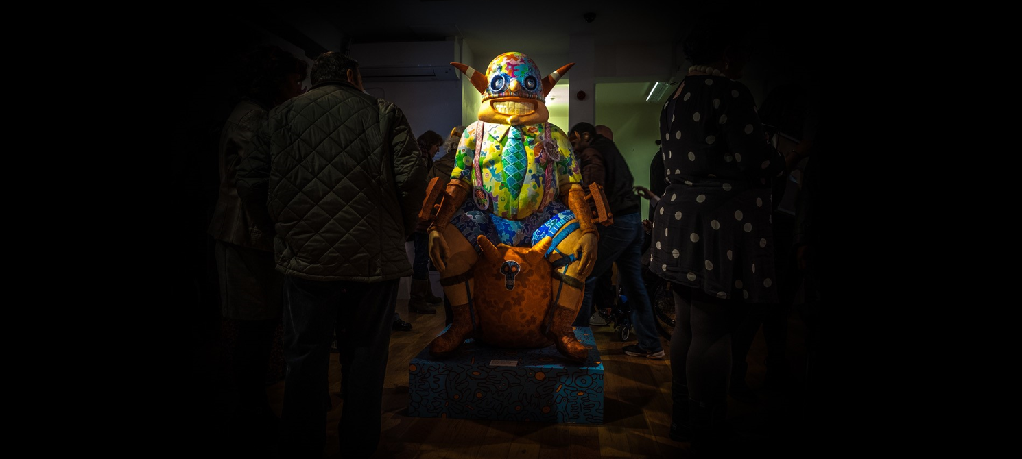 A brightly-coloured, life-size sculpture of a cartoonish stylised human figure covered in patterns stands in a dark room