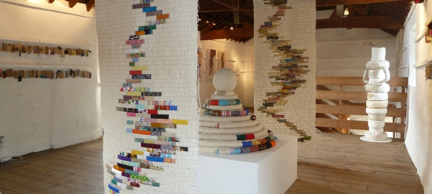 An old barn-style room with white walls and a wooden vaulted ceiling. There are pieces of fabric art hanging from the ceiling and on a plinth. The fabrics are white patchwork with brightly coloured parts