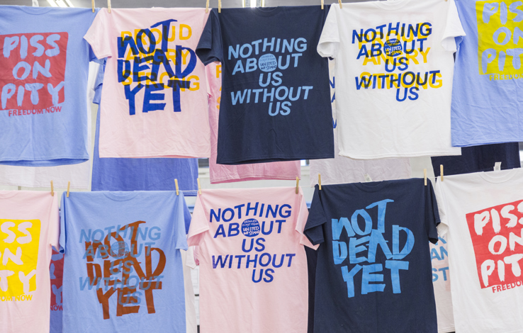 Two rows of tshirts hanging one above the other, all different colours and bearing radical disability rights slogans such as Not dead yet, Piss on pity and Nothing about us without us
