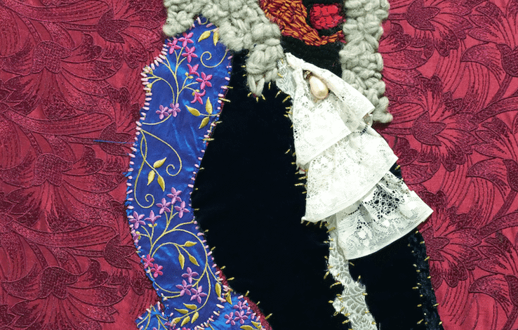 An embroidered and appliqued image of a black man in white powdered wig, which reaches just past the shoulders. He holds a stately posture, standing in front of a red floral background. Patches of fabric have been roughly sewn to illustrate his 17th