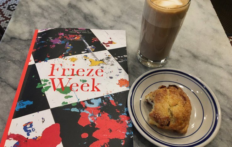 Frieze Week booklet on a table next to a coffee and cake