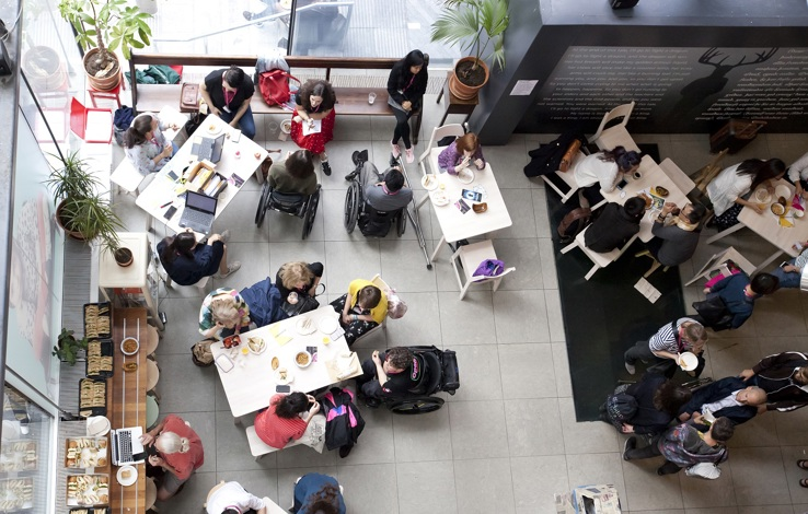 A birds-eye shot of a breakout area, people are sitting and chatting with Unlimited staff sitting in the corner with lanyards talking to various people. There is a food and drinks table to the side and the breakout area is filled with light from larg