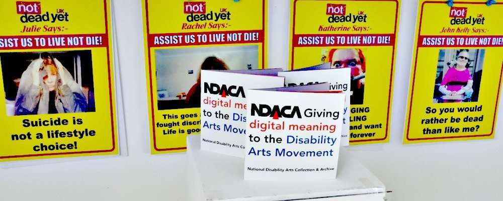 Placards in the NDACA archive on the wall with the catalogue on a plinth in front of them