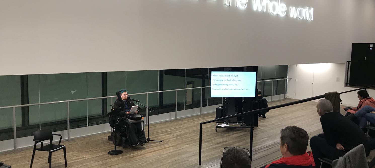 a participant in a motorised wheelchair reads aloud to an audience  in a gallery setting; they have neon lettering above them across a wall