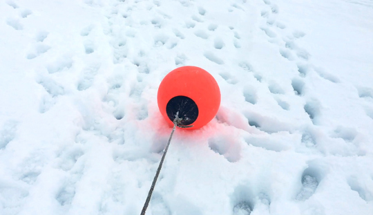 A bright red buoy is laying on a patch of snow covered in footprints