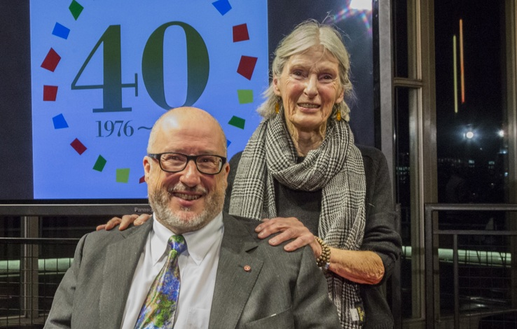 A white man who appears age 60 and a white woman who appears age 75 are next to each other and smiling at the camera