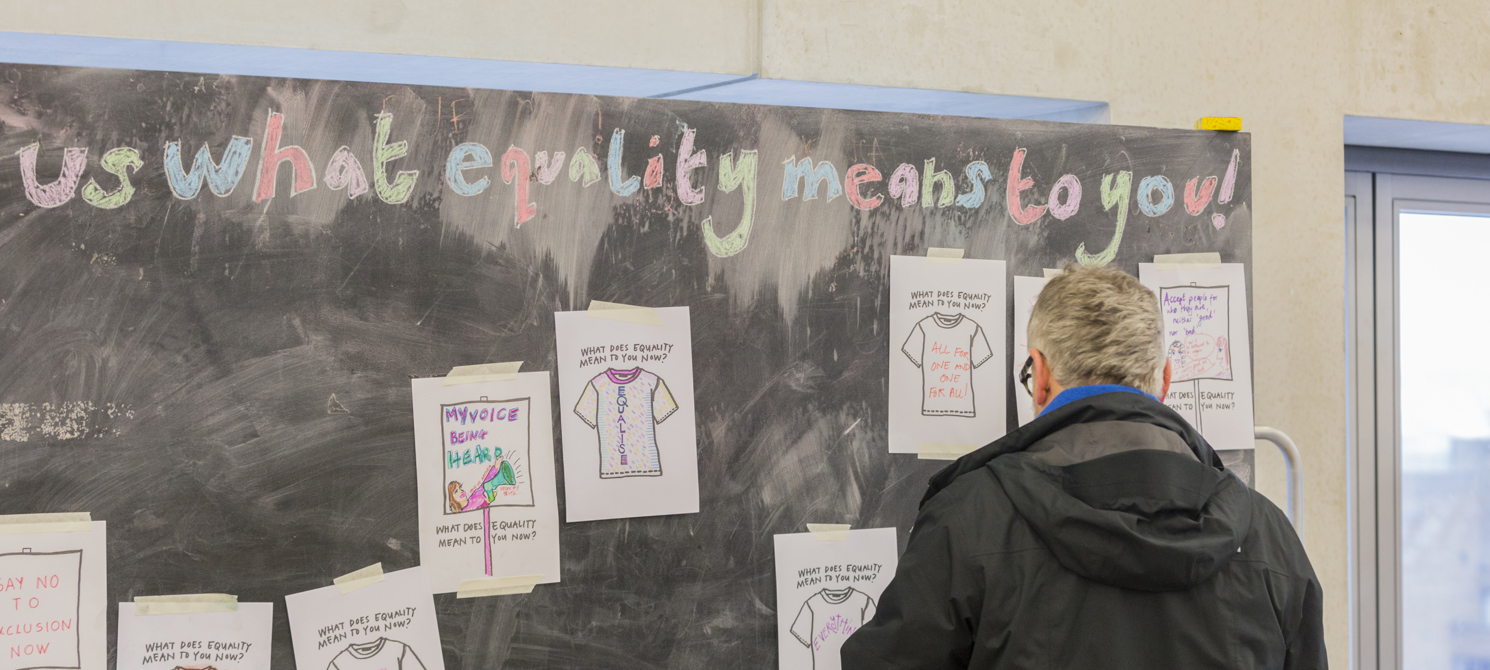 A man standing in front of a blackboard facing away from the camera. The blackboard has some white papers with drawings on them pinned to it, and it has Tell us what equality means to you written along the top in colourful chalk letters