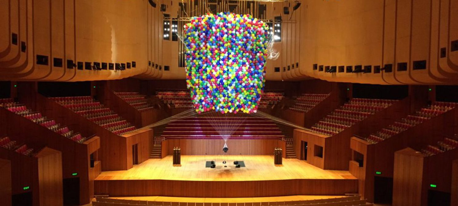 A vast, empty, wood-panelled concert hall (the Sydney Opera House) with a huge bunch of multicoloured helium balloons floating together above the stage with a very small human figure suspended laying down at the bottom of them